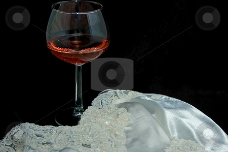 Still Life With Blush Wine and Lingerie stock photo, This still life is an ultimate romantic scene with a glass of blush or pink wine with a beautiful white lingerie against a black background. by Valerie Garner