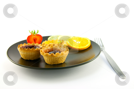 Jam tarts and Fruit stock photo, Red and yellow small jam tarts with slices of lemon, lime, orange and strawberry on a black plate with fork on a white background by Keith Wilson