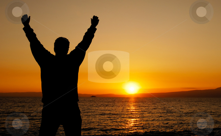 Celebrating life stock photo, Silhouette of a man facing a glorious sunset, with his hands in the air by Andreas Karelias