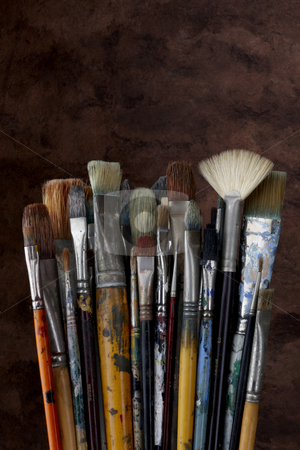 Close up of artist paint brushes on dark textured background stock photo, Dozens of artists brushes shot with dark textured background by James Barber