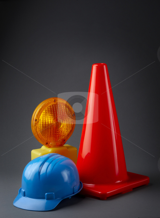 Construction site stock photo, Traffic cone, hard hat and warning light on dark background by James Barber