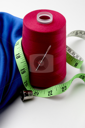 A sewing still life stock photo, A spool of red thread, blue material, green tape measure, sewing needle and thimble by James Barber