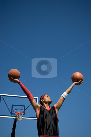 Confident Basketball Player stock photo, A young basketball player holding up two basketballs in the shape of a V. by Todd Arena