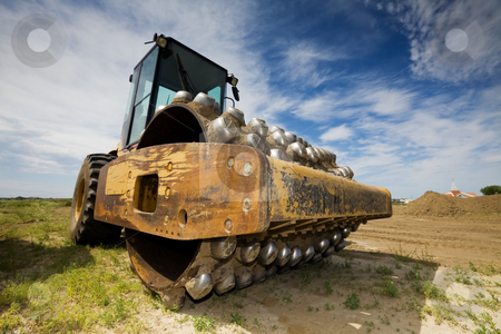 Packer stock photo, A large yellow packer at a construction site low angle view by Steve Mcsweeny