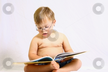 Little boy with glasses reading large book. stock photo, Little boy reading book by Gregory Dean