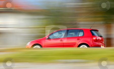 Fast moving red car stock photo, This is a panning shot of a fast moving red small car by Andreas Karelias