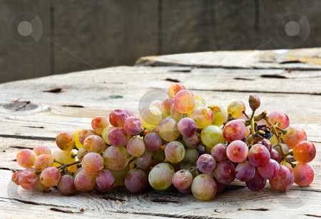 Grapes stock photo, Image shows a bunch of grapes on a wooden table by Andreas Karelias
