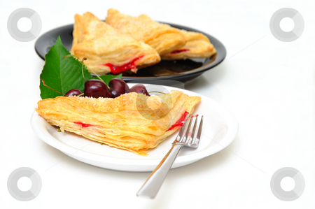Cherry Turnover stock photo, Cherry turnovers with fresh cherries on a white saucer with adiitional parties on a black plate in the background by Lynn Bendickson