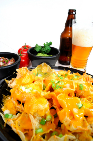 Nacho and Beer stock photo, Plate of cheese nachos with sides of guacamole and salsa with an ice cold bottled beer poured in a glass by Lynn Bendickson