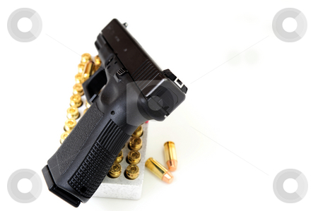 40 Caliber Handgun And Ammunition stock photo, Black pistol also known as a handgun on a white background with a box of copper jacketed bullets under the gun. by Lynn Bendickson