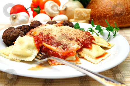 Ravioli And Meatballs stock photo, Thee cheese ravioli with parmesean cheese sprinkled on top, small meatballs on the side. Fresh vegetables, cheese and bread in the background. by Lynn Bendickson