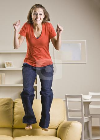 Teenage girl jumping on sofa stock photo, Teenage girl jumping on sofa by Jonathan Ross