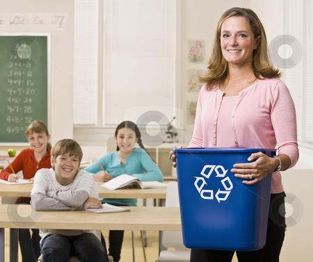 Teacher holding recycling bin stock photo, Teacher holding recycling bin by Jonathan Ross