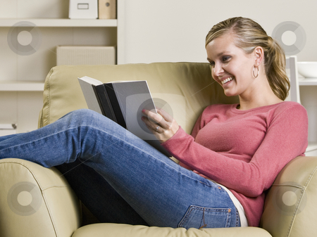 Teenage girl reading book in chair stock photo, Teenage girl reading book in chair by Jonathan Ross