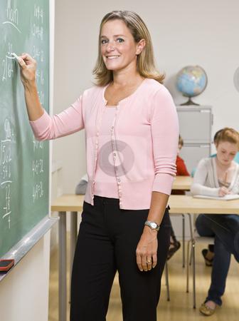 Teacher writing on blackboard stock photo, Teacher writing on blackboard by Jonathan Ross