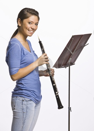 Teenage girl playing oboe stock photo, Teenage girl playing clarinet by Jonathan Ross