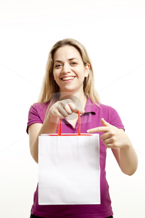 Young woman shows paper shoppings bag stock photo, Young woman shows the paper shoppings bag with the shoppings that she made by Marios Karampalis