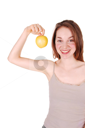 Young girl holding up apple. stock photo, A smiling young girl holding up an yellow apple to show that a good diet  gave her the nice slim figure she has. On white background. by Horst Petzold