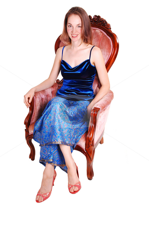 Pretty girl in armchair. stock photo, A lovely long haired woman in an blue dress and Indian pants sitting in the pink armchair in high heels and smiling. On white background by Horst Petzold