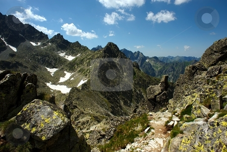 Walking path in mountains among sharp peaks stock photo, Walking path in mountains among sharp peaks by Juraj Kovacik