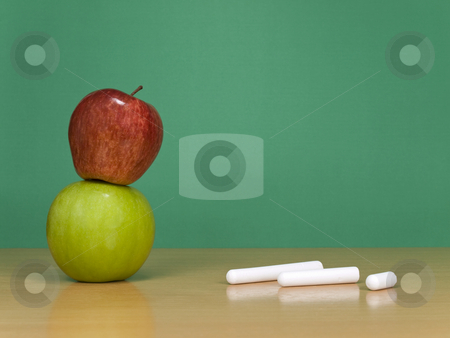 At the classroom stock photo, Some chalks and a red apple over a green one. A green chalkboard on the background. by Ignacio Gonzalez Prado