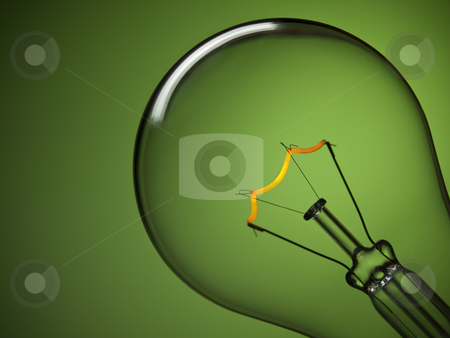 Bulb light over green stock photo, Close up on a turned on light bulb over a green background. Tungsten glowing filament. by Ignacio Gonzalez Prado