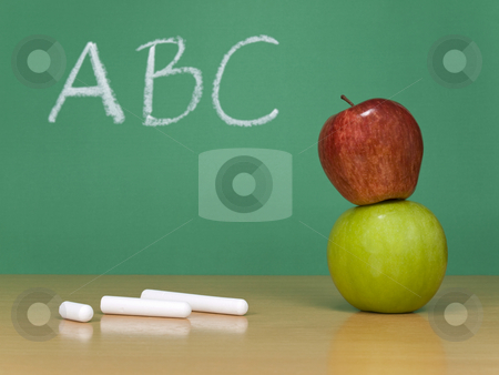 ABC stock photo, ABC written on a chalkboard. Some chalks and a red apple over a green one on the foreground. by Ignacio Gonzalez Prado