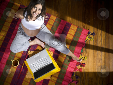 Modern mom stock photo, Top view of a young pregnant woman seated on a colorful rug with a laptop computer and a cup of tea. by Ignacio Gonzalez Prado
