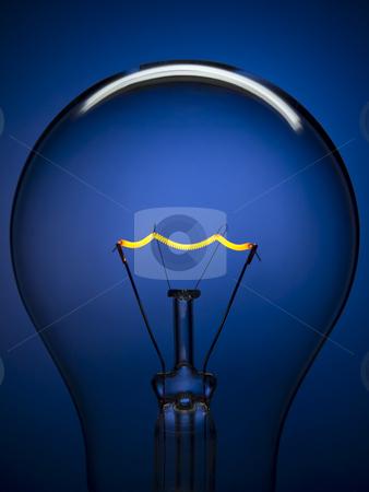 Bulb light over blue stock photo, Close up on a transparent light bulb over a blue background. Tungsten glowing filament. by Ignacio Gonzalez Prado