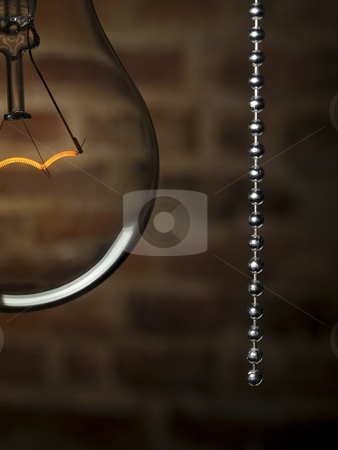 Turn off the light stock photo, Close up on a transparent light bulb with a pull switch over a brick wall background. by Ignacio Gonzalez Prado