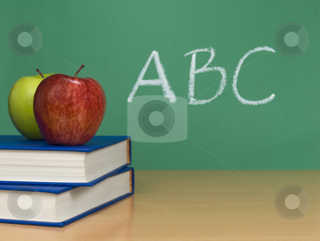 ABC stock photo, ABC written on a chalkboard. Two apples over books on the foreground. by Ignacio Gonzalez Prado