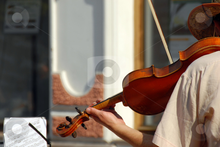 Street musician stock photo, Street violinist playing a violin with music sheet by Julija Sapic