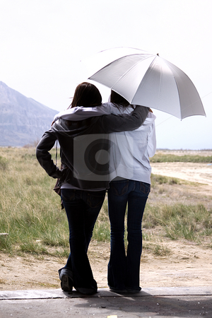 Teenage Girls Looking Out the Door stock photo, Teenage Girls Looking Out the Door with an Umbrella by Mehmet Dilsiz