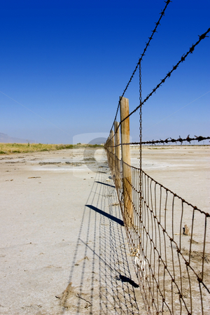 Fence Under Clear Skies stock photo, Fence in the Salt Lake in Summer in Utah with Clear Blue Skies by Mehmet Dilsiz