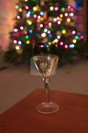 Celebrating the Holidays with Wine stock photo, Wine Glass with the Christmas lights on the background by Mehmet Dilsiz