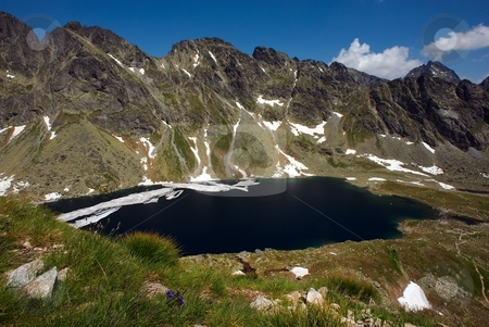 Melting big mountain lake stock photo, Big mountain lake in summer day with some ice on surface by Juraj Kovacik