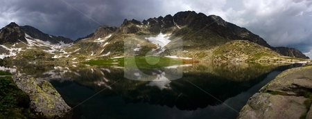 Mountain lake before storm stock photo, Mountain lake before summer storm wide panorama by Juraj Kovacik