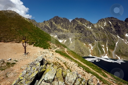 Crossroad of mountains paths in summer stock photo, Crossroad of mountains paths with partly view on a lake in summer sunny day by Juraj Kovacik