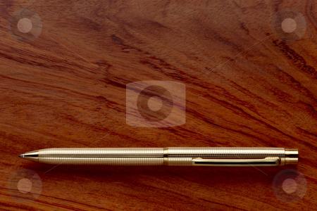 Gold pen on wooden desk stock photo, Gold pen shot on grainy wooden desk by James Barber