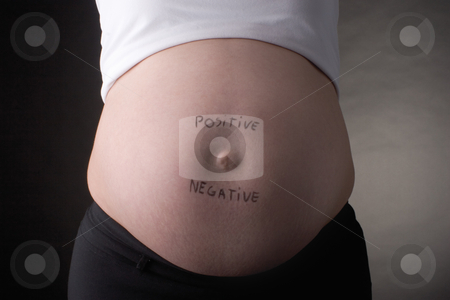 Positive negative belly stock photo, Seven month pregnant belly with positive and negative written on stomach by Yann Poirier