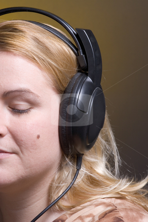 Women listing stock photo, Women listing to relaxing music with her eyes close by Yann Poirier