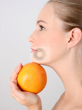 Healthy Lifestyle stock photo, Beautiful young model holding an orange under her chin by Vanessa Van Rensburg