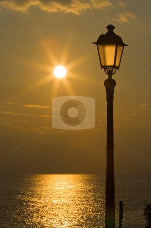 Reflections stock photo, Sun reflected on the sea and streetlight at sunset in Mediterranean sea by ANTONIO SCARPI