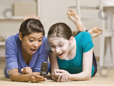 Teenage girls text messaging on cell phone stock photo, Teenage girls text messaging on cell phone by Jonathan Ross