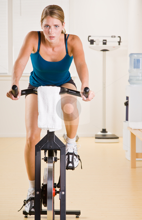 Woman riding stationary bicycle in health club stock photo, Woman riding stationary bicycle in health club by Jonathan Ross