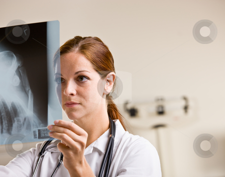 Doctor reviewing x-rays in doctor?s office stock photo, Doctor reviewing x-rays in doctor?s office by Jonathan Ross