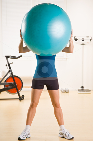 Woman holding exercise ball in health club stock photo, Woman holding exercise ball in health club by Jonathan Ross