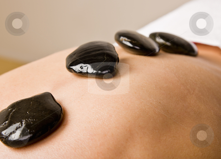 Woman receiving hot stone therapy massage stock photo, Woman receiving hot stone therapy massage by Jonathan Ross