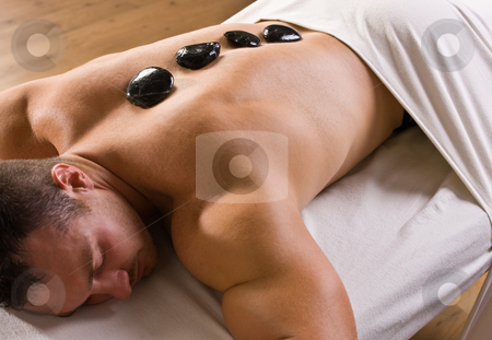 Man receiving hot stone therapy massage stock photo, Man receiving hot stone therapy massage by Jonathan Ross