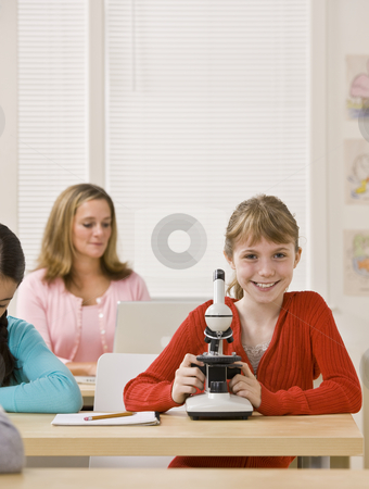 Student looking into microscope in classroom stock photo, Student looking into microscope in classroom by Jonathan Ross